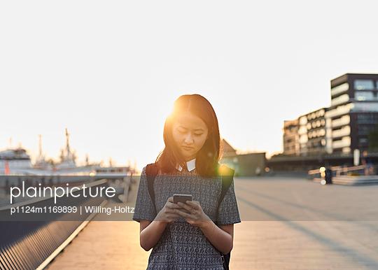 Asiatin mit Smartphone im Gegenlicht - p1124m1169899 von Willing-Holtz