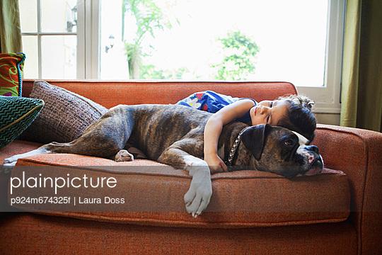 Girl lying on sofa with pet dog