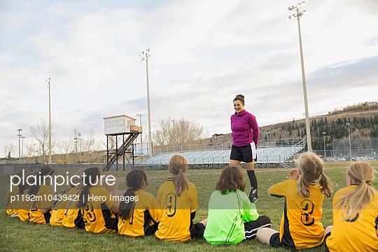 Coach talking to girls soccer team