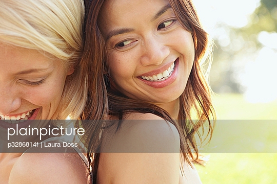 Two women back to back, laughing and smiling