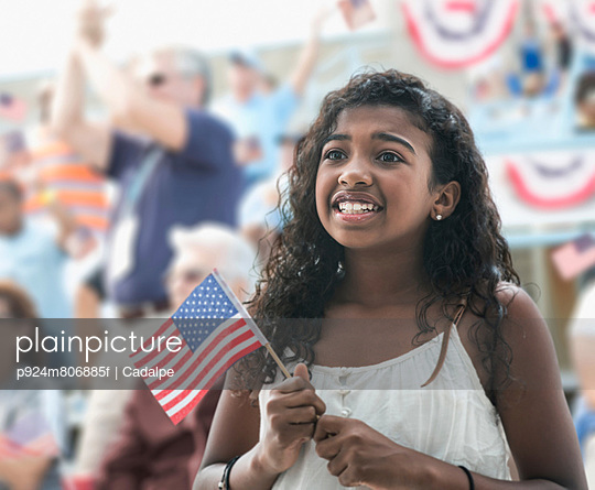 Girl holding american flag; looking anxious