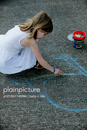 Mädchen malt mit Straßenkreide einen Vogel auf den Asphalt - p1212m1145994 von harry + lidy