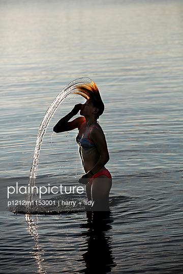 Mädchen im See macht Waserstrahl mit dem nassen Haar - p1212m1153001 von harry + lidy