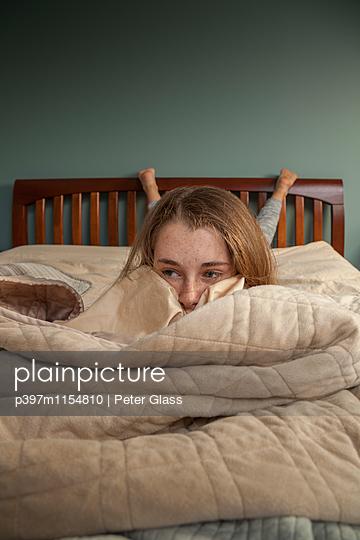 Teenager auf dem Bett hat Tagträume - p397m1154810 von Peter Glass