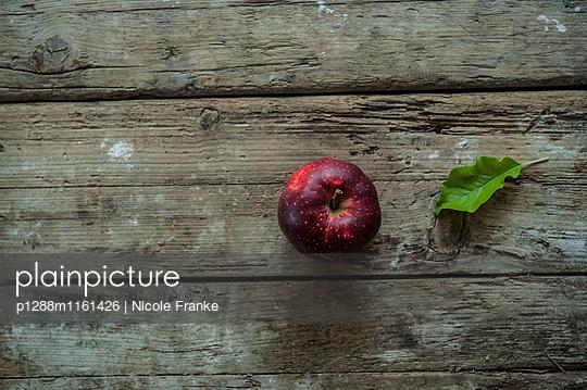 Roter Apfel auf Holztisch - p1288m1161426 von Nicole Franke