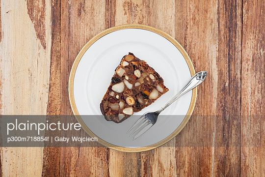 Slice of Christmas fruit cake in plate
