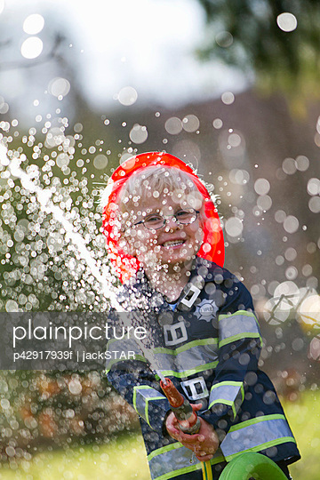 Boy in fireman costume playing with hose