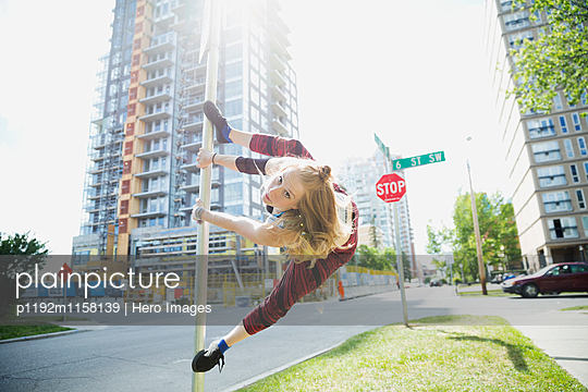 Young woman doing parkour on pole in urban street