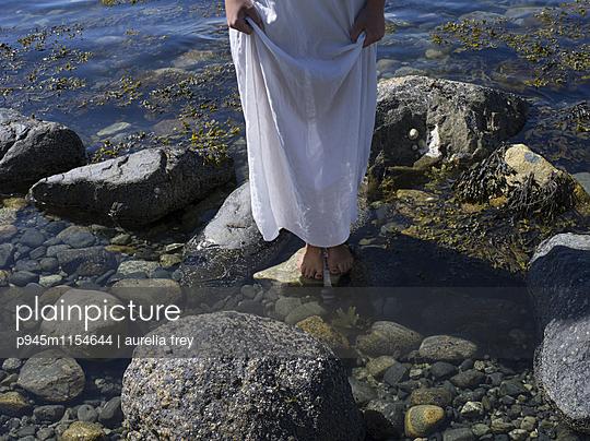 Junge Frau im weißen Kleid am Ufer - p945m1154644 von aurelia frey
