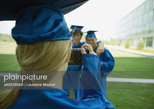 Female graduate taking photo of friends