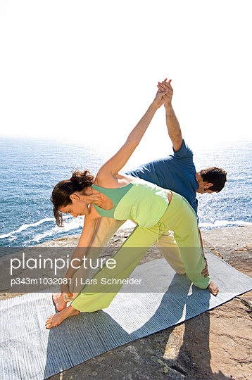 A man and woman practicing yoga on a rocky outcrop above the Pacific Ocean at North Curl Curl, one of Sydneys Nor