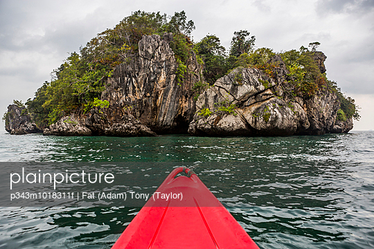 The tip of a sea kayak in the ocean while looking at a rock formation off the coast of Krabi, Thailand.