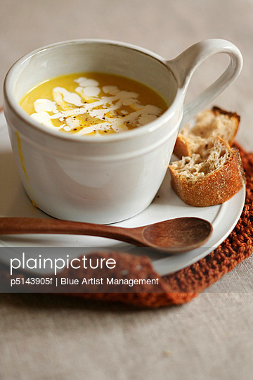 Cup of pumpkin soup, white background