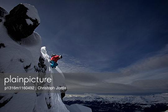 Skifahrerin springt von einem Vorsprung, Chandolin, Anniviers, Wallis, Schweiz - p1316m1160492 von Christoph Jorda