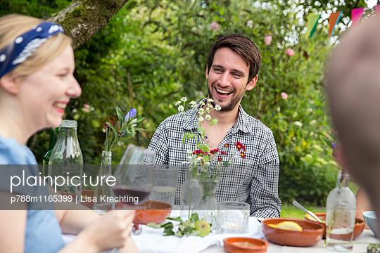 Freunde feiern eine Gartenparty - p788m1165399 von Lisa Krechting
