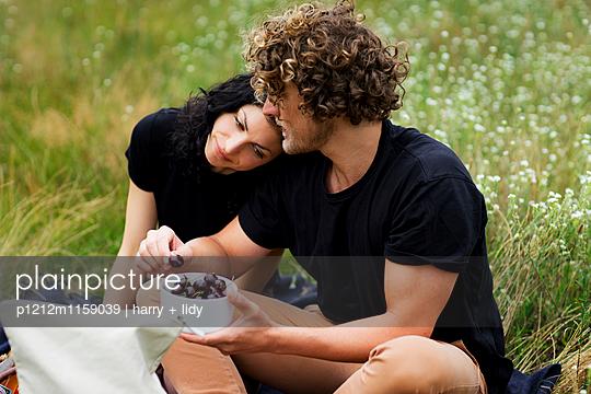 Paar mit Kirschen auf der Wiese - p1212m1159039 von harry + lidy