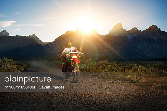 Man riding motorcycle along mountain road