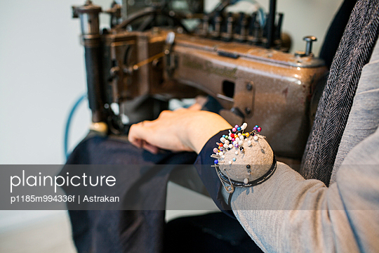 Midsection of male fashion designer wearing pin cushion while using sewing machine in jeans factory