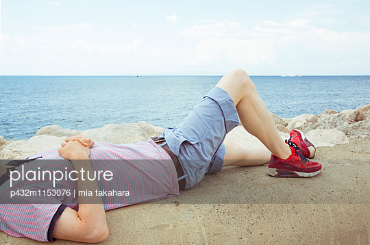 Mann schläft am Meer - p432m1153076 von mia takahara