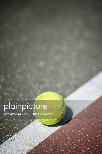 Tennis Ball Resting on Court Line