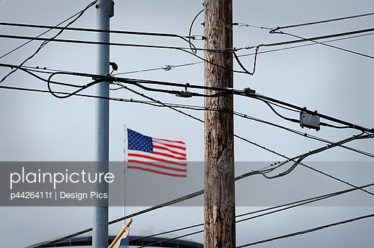 American flag behind phone wires and electrical wires