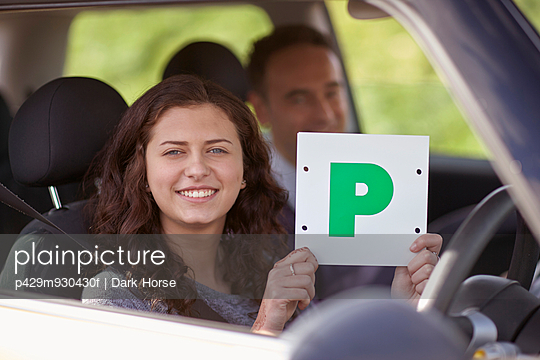 Female learner driver holding Passed Plate