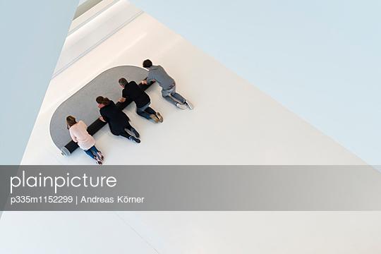 Gemeinsam einen Teppich ausrollen - p335m1152299 von Andreas Körner