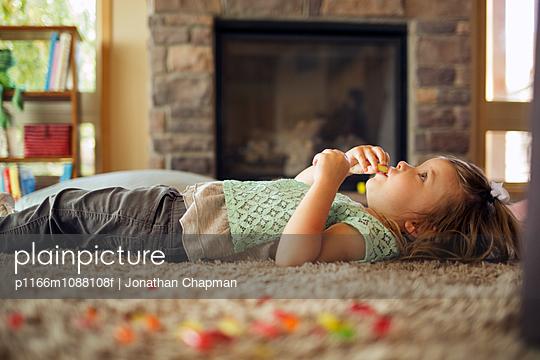 Little girl lying on carpet in living room