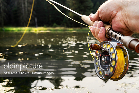 Hand holding fishing rod with line in water