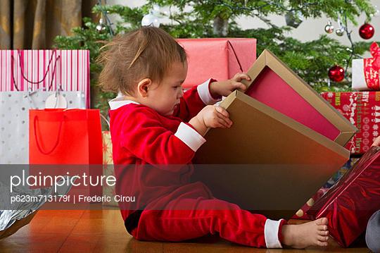 Baby girl opening Christmas present