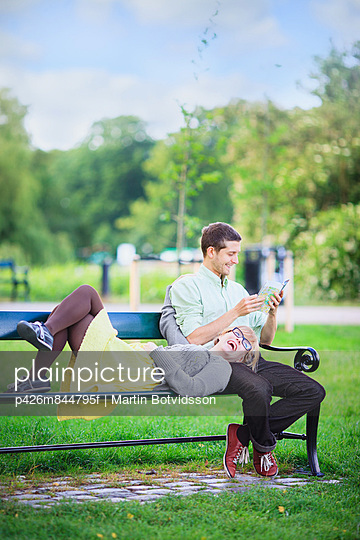 Happy couple relaxing on park bench