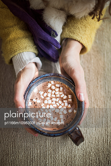 Hands of woman holding mug of coffee with marshmallows