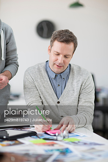 Mature man making notes on desk in creative office