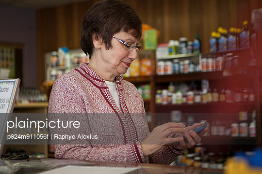 Owner of health foods store using smartphone