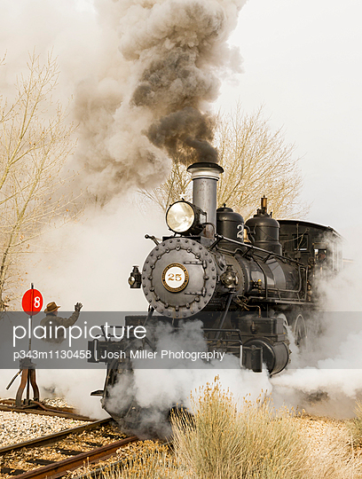 Man waves to steam train as it leaves the station
