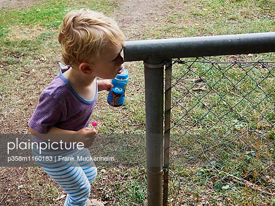 Junge schaut in ein Rohr - p358m1160183 von Frank Muckenheim