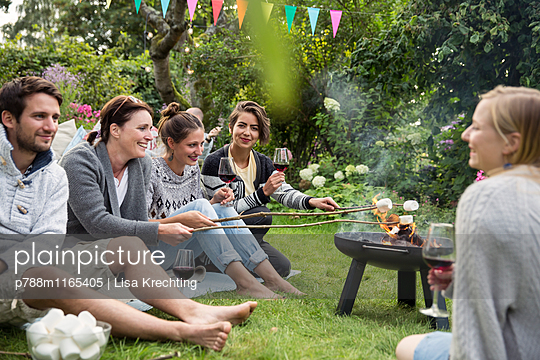 Freunde auf einer Gartenparty rösten Marshmallows  - p788m1165405 von Lisa Krechting