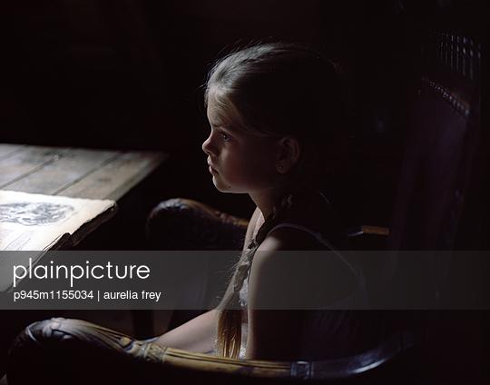 Mädchen sitzt träumend auf einem Stuhl - p945m1155034 von aurelia frey
