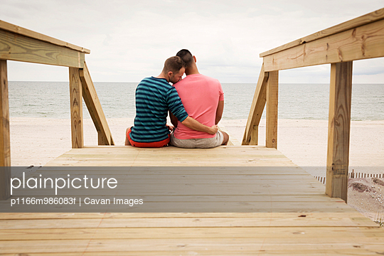 USA, New York State, New York City, Long Island, Gay couple embracing on wooden steps leading to beach
