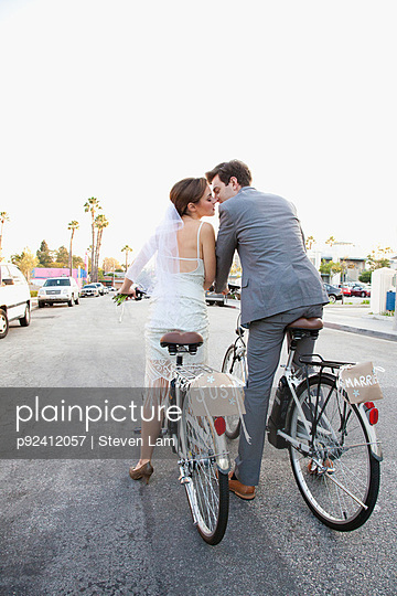 Young newlywed couple kissing on bicycles in street