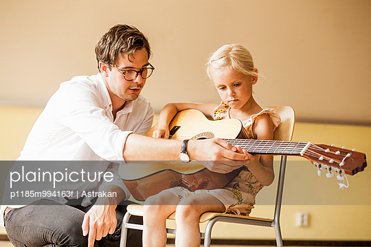 Male teacher teaching girl to play guitar