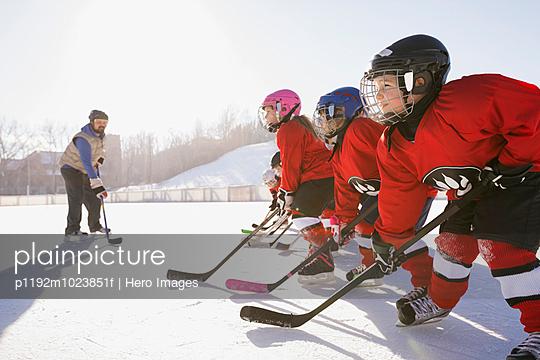 Coach training hockey players on ice rink