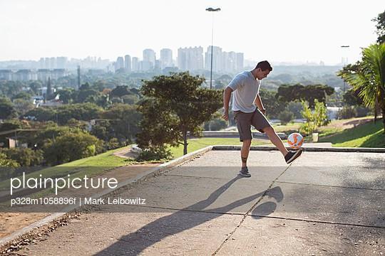 Man kicking soccer ball in park