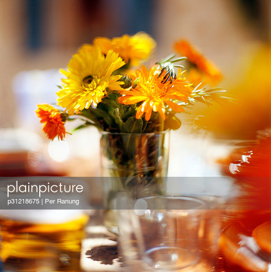 Yellow flowers in a vase on a set table.