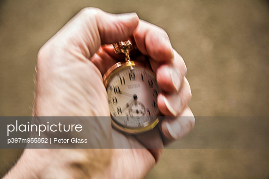 Man\'s hand holding a pocket watch.