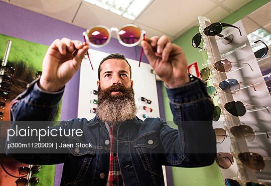 Bearded man in optical store chosing sunglasses