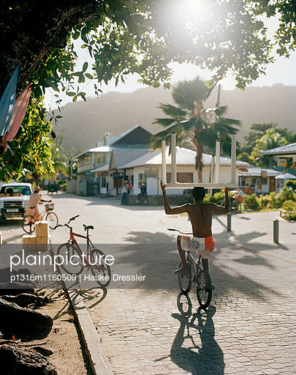 Radfahrer transportiert Tisch auf der Hauptstrasse am Morgen, La Passe, La Digue and Inner Islands, Republik Seychellen, Indischer Ozean - p1316m1160509 von Hauke Dressler