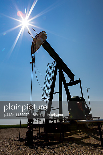 Low angle view of a pump jack with a sun burst in the blue sky; Acme, Alberta, Canada