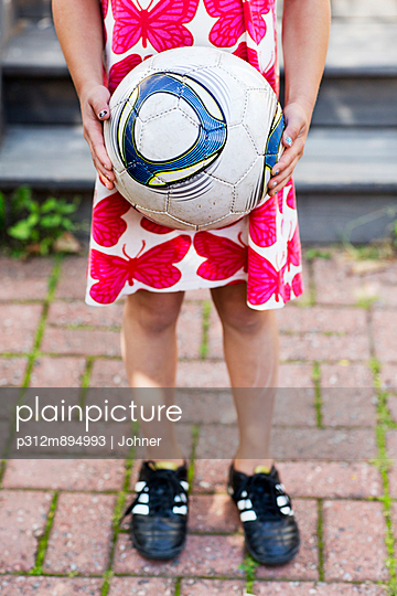 Girl holding soccer ball, low section, Sollentuna, Stockholm, Sweden