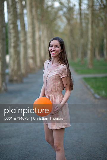 A young woman holding an orange ball, standing in a park